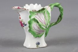A Longton Hall cream jug with openwork twist handle and leaf relief decoration and enamel floral