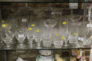 A quantity of cut glass pedestal glasses, including wines, brandies and liqueurs, a decanter and two