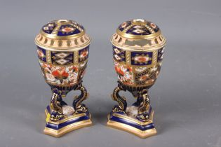 A pair of Davenport Imari decorated pot-pourri vases and covers (one repaired with losses), on