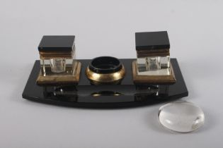"A 1930s black glass desk inkstand, 11"" wide (two feet missing) and a desk weight"