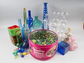 A Mdina pink glass scent bottle and stopper, a number of coloured glass bottles, ten Babycham coups,
