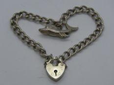 A silver charm bracelet having hallmarked heart padlock clasp,
