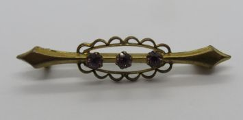 A yellow metal brooch set with three round cut purple stones, 4cm, 1.5g.