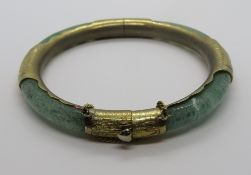 A jade bangle with gilt metal fittings, slightly a/f, 7.5cm ext dia, 6cm int dia.