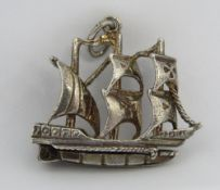 An unusual charm or pendant in the form of a three masted ship bearing Maltese Cross upon the sails,