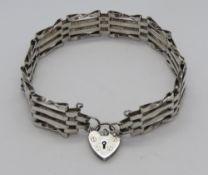 A silver four bar bracelet having hallmarked heart padlock clasp.