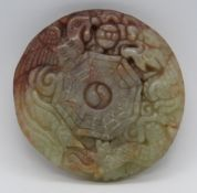 An unusual two colour carved jade disc pendant having phoenix and dragon design upon,