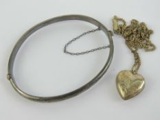 A silver heart shaped pendant on fine wh