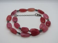 A hot pink hard stone necklace having 92