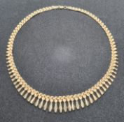 A 9ct gold articulated necklace having three-row panel chain with graduated 'tassles' upon,