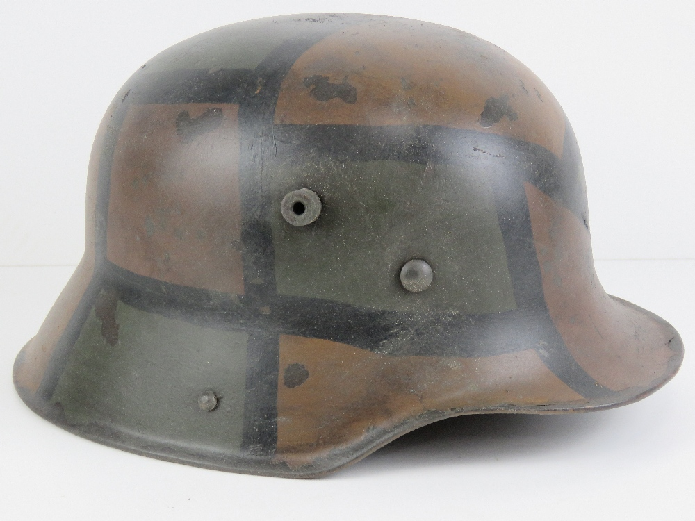 A reproduction WWI German helmet in camouflage paint, with liner.