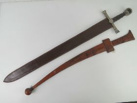 A Sudanese sword with double edged steel blade and leather hilt with matching leather scabbard.