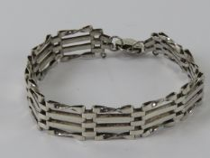 A silver gate link bracelet having London hallmarked heart padlock clasp.