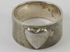 An Arts and Crafts style silver ring having central raised heart motif, graduated band 1.