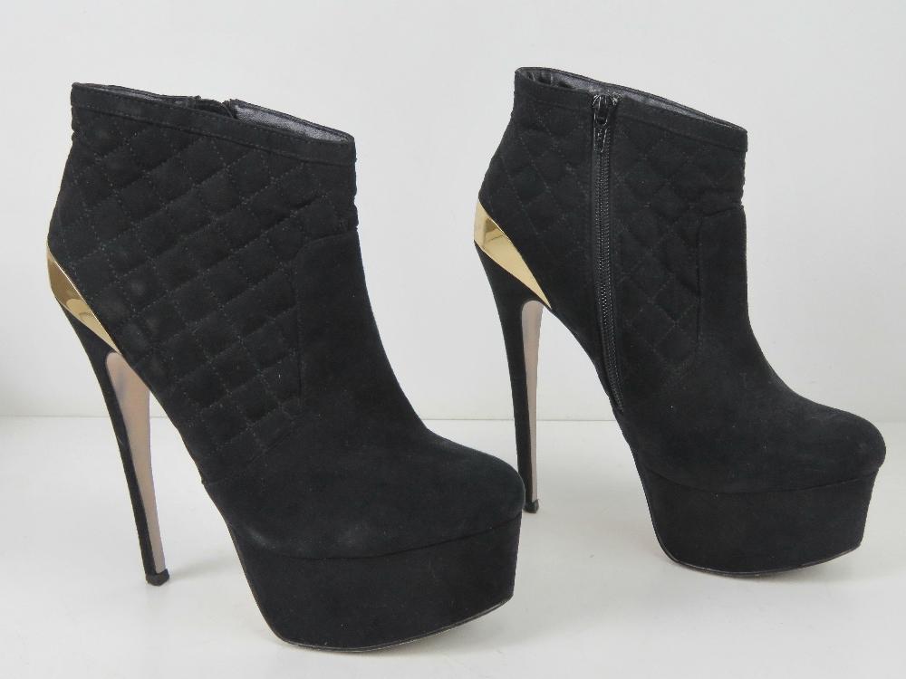 A pair of black velvet platform ankle bo