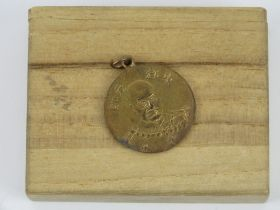 A WWII Japanese medal with a face of the emperor in box.