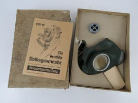 A WWII German civilian gas mask and filter in box with instructions, having German marks.