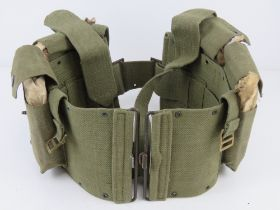 A green canvas BAR belt having four BAR magazines within.