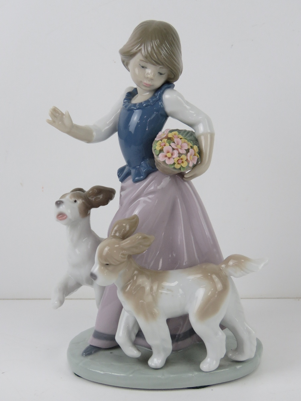 Lladro figurine 5761 'Out For A Romp' a girl with two dogs and a basket of flowers under her arm,