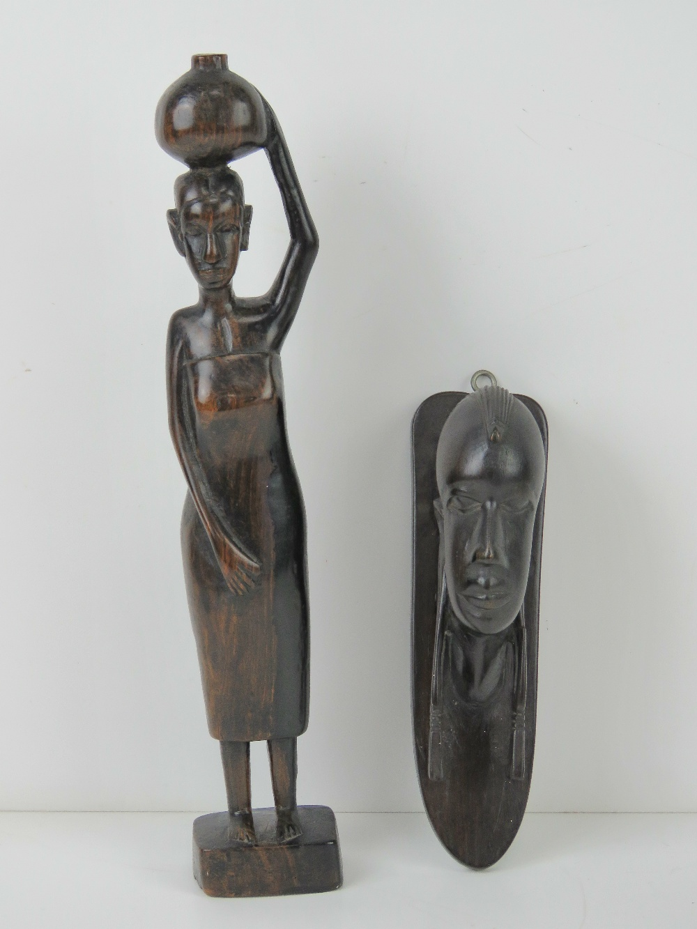 A carved African hardwood figurine of a woman standing 31cm high,