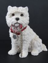A figurine of a Westie with collar holding its leash in mouth, 23.5cm high.