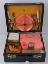 A vintage picnic case by Ilat with contents including beakers, teacups, storage boxes, plates,
