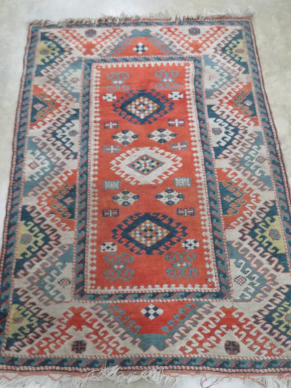 A teal and orange ground woollen rug hav