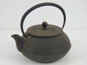 An oriental cast iron teapot having rais