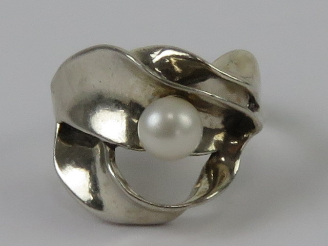 An abstract design silver and pearl ring