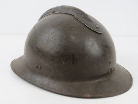 A French 1939-1943 helmet having liner and chin strap, badges removed.