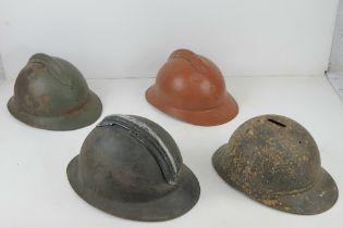 Four WWI/WWII French helmets.