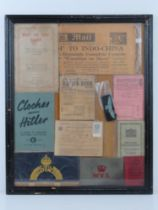 A framed montage of WWII items inc rations books, identity card, driving licence, arm bands,