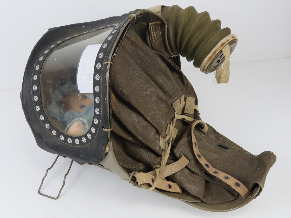 A WWII c1940s babys gas mask having rubber hose.