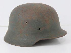 A WWII German helmet, liner deficient.