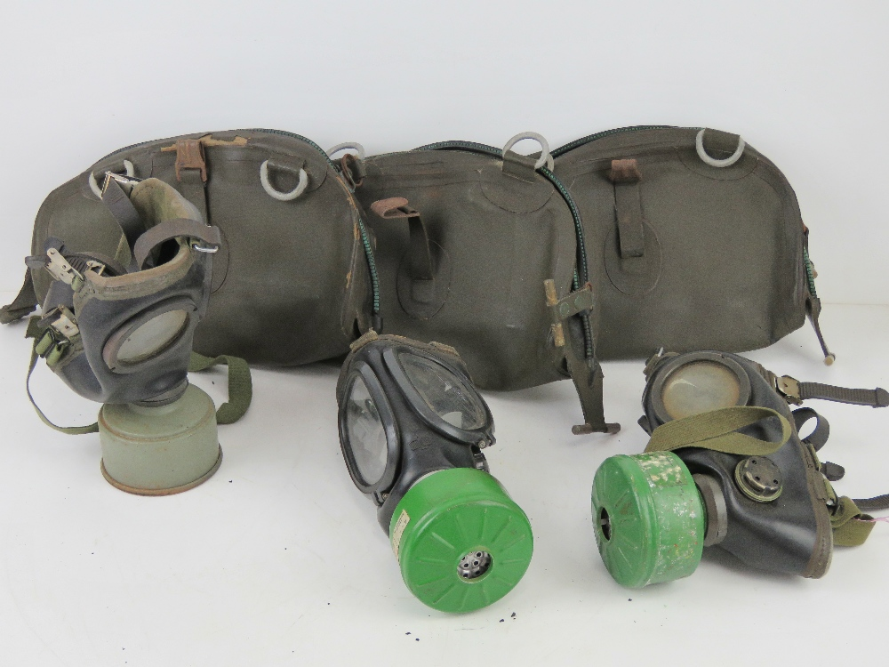 Three German Bundeswehr Draeger/CTG-RA gas masks with filters in carry cases.