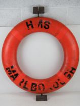 A HMS Marlborough life preserver ring having mounting hooks attached.