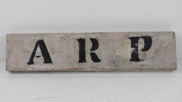 A wooden ARP sign 'found on door behind wall in Northampton'. 35 x 8cm.