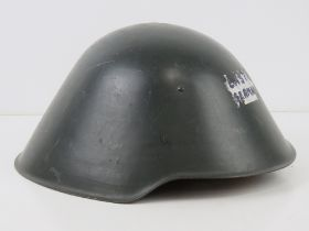 A late 20thC East German helmet marked within III/57, having chin strap and liner.