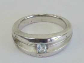 A HM silver ring having central aquamarine to the wide two sectional band, hallmarked for Sheffield,