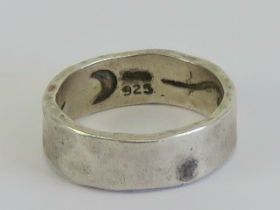 A Mary Cayatineto Navajo hand planished silver ring having Native American symbols within,