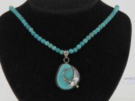 A floral silver and turquoise pendant, having large teardrop cabachon in frame stamped 925 approx 4.