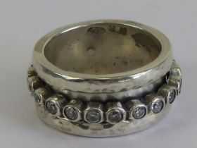 A worry ring (stress ring / fidget ring) having central white stone set rotating band,