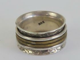 A handmade worry ring (stress ring / fidget ring) having four rotating central bands, stamped 925,