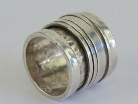 An unusually wide handmade worry ring (stress ring / fidget ring) having five rotating central