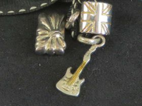 Links of London; three silver charms having Links hallmark upon in the form of a guitar,
