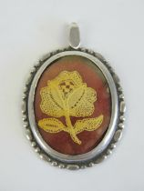 A HM silver pendant having lacework rose within, hallmarked for Birmingham 1981, 5.3cm in length.
