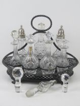 A large silver plated and cut glass cruet set having two cut glass sugar castors with HM silver tops