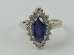A silver cocktail ring having central marquise cut blue/purple stone surrounded by round cut white
