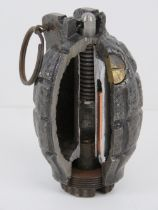 An inert WWI Mills No.36 grenade having cut away section for display, with spoon and pin.