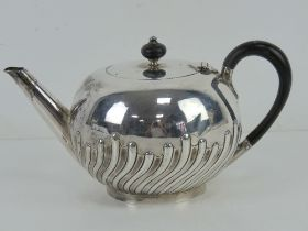 A Victorian HM silver teapot having ebonised wooden handle and finial,